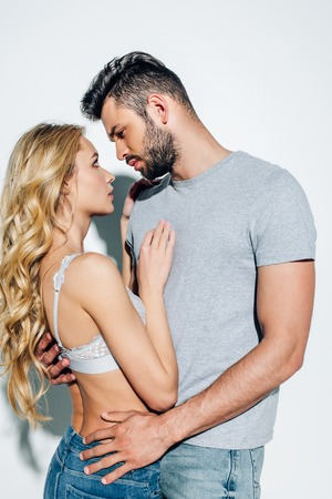 handsome man looking at attractive blonde girl in lace bra on white Фото со стока