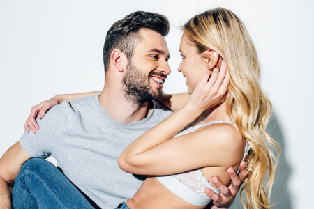 happy bearded man looking at attractive blonde girl on white