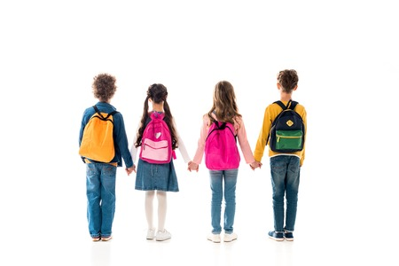 Back view of schoolchildren with backpacks holding hands isolated on white background