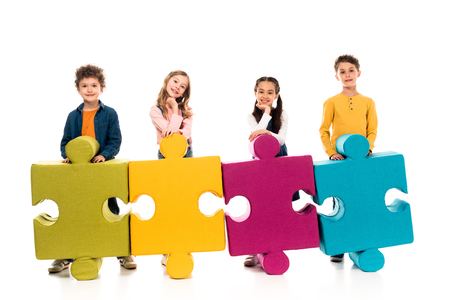 Full length view of kids with colorful jigsaw puzzles on white background Stock Photo