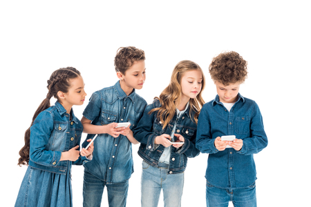 four kids in denim clothes using smartphones isolated on white