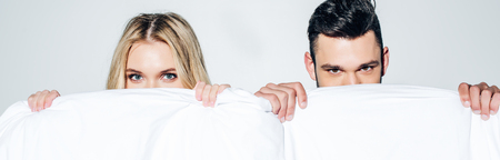 Panoramic shot of blonde woman and man looking at camera while covering face with blanket on white background Stock fotó