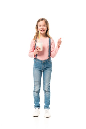 Full length view of smiling kid holding milkshake and showing thumb up isolated on white background