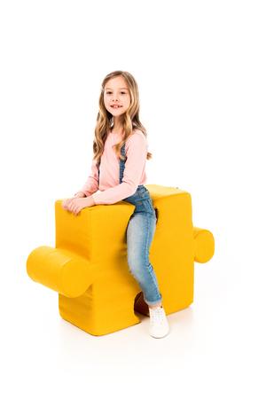 Smiling kid sitting on big jigsaw puzzle on white background Stock Photo
