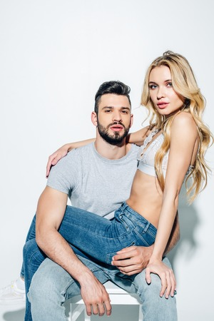 attractive blonde woman looking at camera with handsome man on white