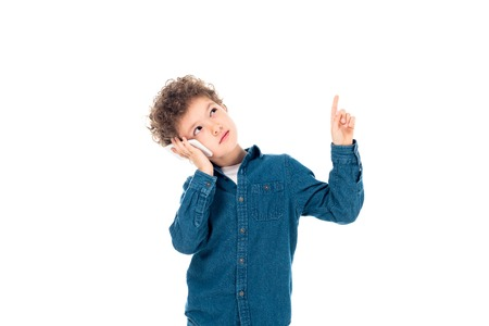 pensive curly kid in denim shirt talking on smartphone and showing idea sign isolated on white Фото со стока