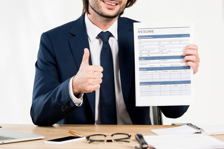 cropped view of cheerful recruiter showing thumb up and holding resume