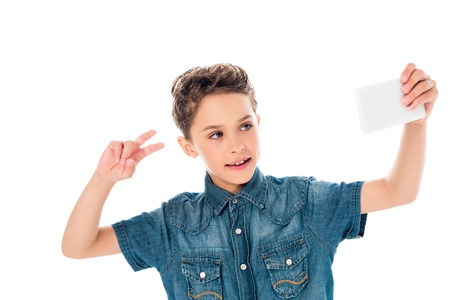Kid in denim shirt taking selfie and showing peace sign isolated on white background Stock Photo