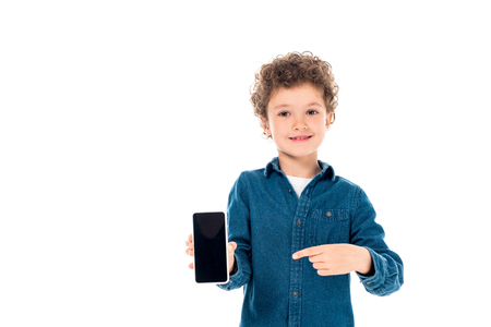 front view of curly child in denim shirt pointing with finger at smartphone with blank screen isolated on white