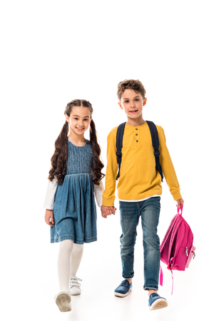 Full length view of schoolchildren with backpacks holding hands isolated on white background