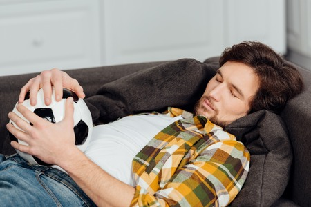 tired man holding football and sleeping on couch Stock Photo
