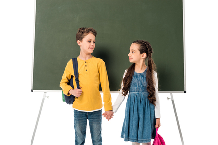 two schoolchildren with backpacks holding hands near blackboard isolated on white