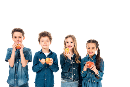 four children in denim clothes eating apples isolated on white