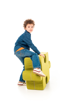 Kid in denim clothes with big jigsaw puzzle on white background Stock Photo