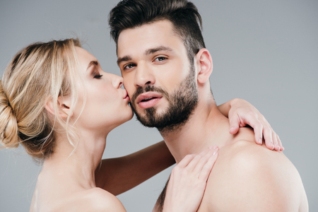 Attractive nude woman kissing cheek of handsome bearded man on grey background Standard-Bild