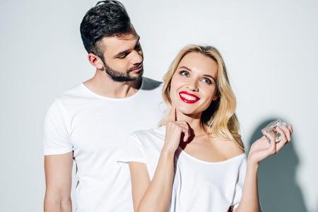 Gut aussehender Mann, der fröhliches blondes Mädchen betrachtet, das Parfüm auf weißem Hintergrund aufträgt Standard-Bild