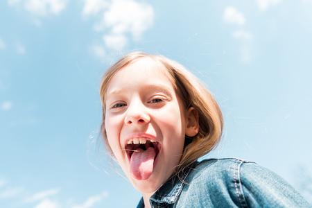 Lage hoekmening van gelukkig kind dat tong onder de hemelachtergrond toont