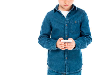 partial view of kid in denim shirt using smartphone isolated on white