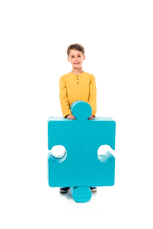Full length view of smiling kid with big jigsaw puzzle on white background