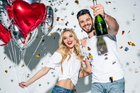 selective focus of cheerful bearded man holding bottle of champagne near woman with balloons near confetti on white 版權商用圖片