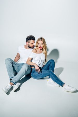 Handsome man sitting and looking at attractive blonde girl on white background