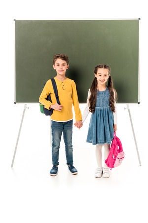 full length view of two schoolchildren with backpacks holding hands near blackboard isolated on white