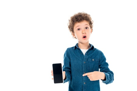 front view of shocked kid in denim shirt pointing with finger at smartphone with blank screen isolated on white