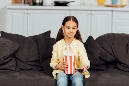 cheerful kid holding remote controller while sitting on sofa with bucket of popcorn Imagens