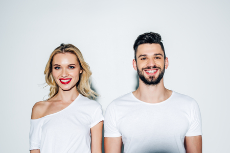 Cheerful bearded man and happy blonde girl looking at camera on white background Stockfoto