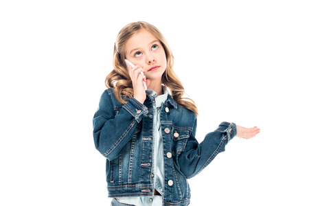 kid in denim jacket talking on smartphone and looking up isolated on white