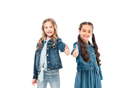 Two smiling kids in denim clothes showing thumbs up isolated on white background