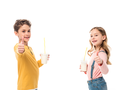 Two kids holding milkshakes and showing thumbs up isolated on white background Stock Photo