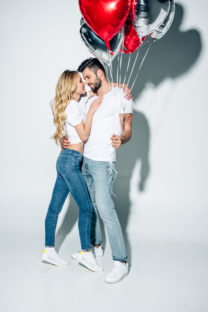 cheerful blonde woman hugging handsome man standing in jeans with balloons on white
