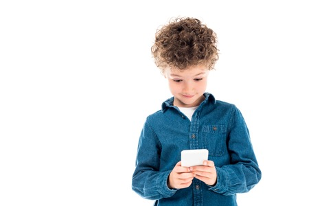 cute curly kid in denim shirt using smartphone isolated on white
