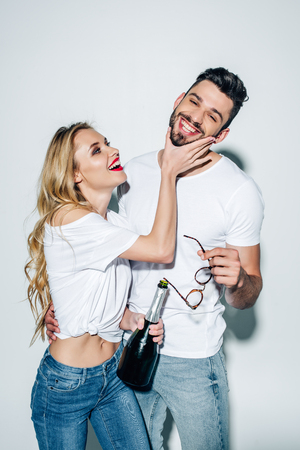 cheerful blonde girl holding bottle and touching face of handsome man on white