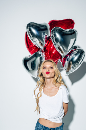 attractive blonde girl with duck face holding balloons on white