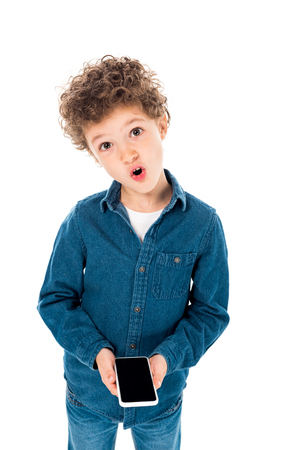 surprised child in denim shirt holding smartphone with blank screen isolated on white