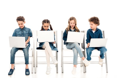 Four kids in denim clothes sitting on chairs and using laptops on white background 스톡 콘텐츠