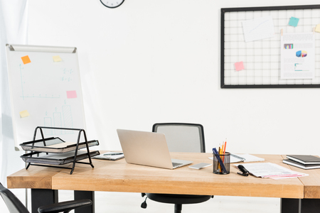 Modern office with white board and laptop on wooden desk Stock Photo