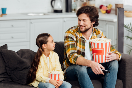 happy man looking at cute daughter while holding bucket of popcorn and remote controller