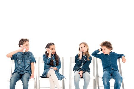 Four kids in denim clothes sitting on chairs and talking on smartphones isolated on white background