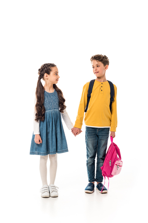 full length view of schoolchildren with backpacks holding hands isolated on white Фото со стока