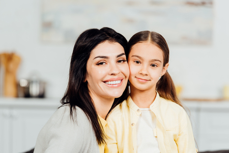 Happy child looking at camera with cheerful mother at home