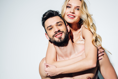 Cheerful blonde young woman hugging happy bearded man on white background