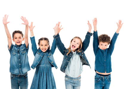 front view of four kids in denim clothes smiling with hands up isolated on white