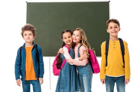 Smiling schoolgirls embracing near blackboard isolated on white background