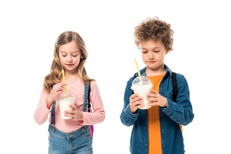 two schoolkids with backpacks holding milkshakes isolated on white 写真素材