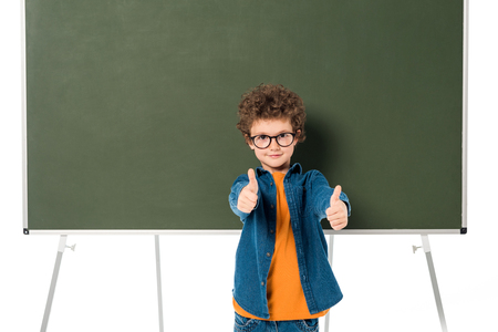 Smiling schoolboy in glasses standing near blackboard and showing thumbs up isolated on white background