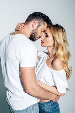 handsome man with closed eyes hugging blonde girl on white