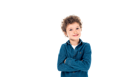 smiling curly kid in denim shirt standing with crossed arms isolated on white Фото со стока